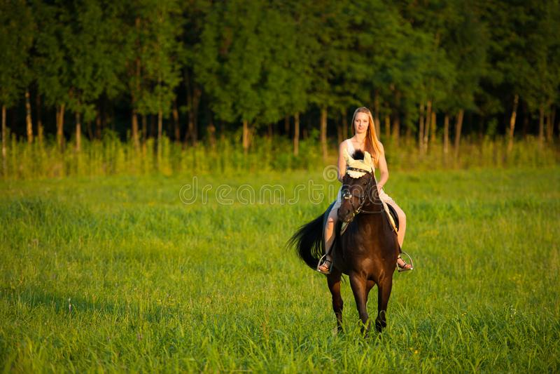 Giro attivo della giovane donna un cavallo in natura immagini stock