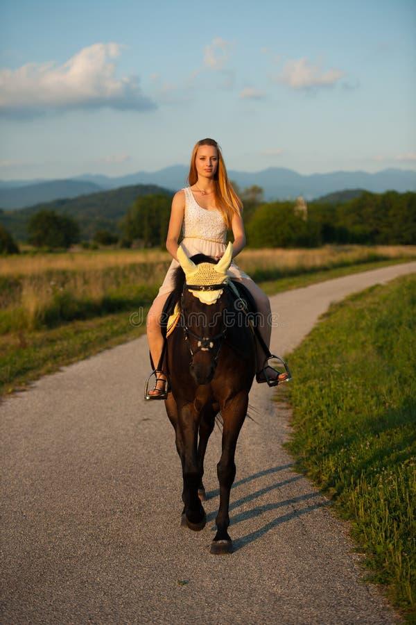 Giro attivo della giovane donna un cavallo in natura fotografia stock