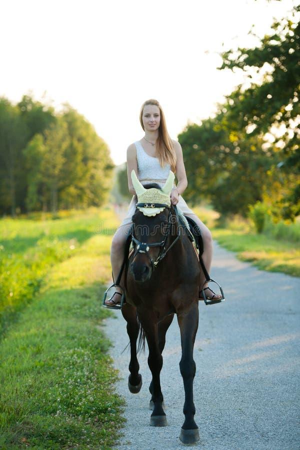 Giro attivo della giovane donna un cavallo in natura fotografia stock libera da diritti