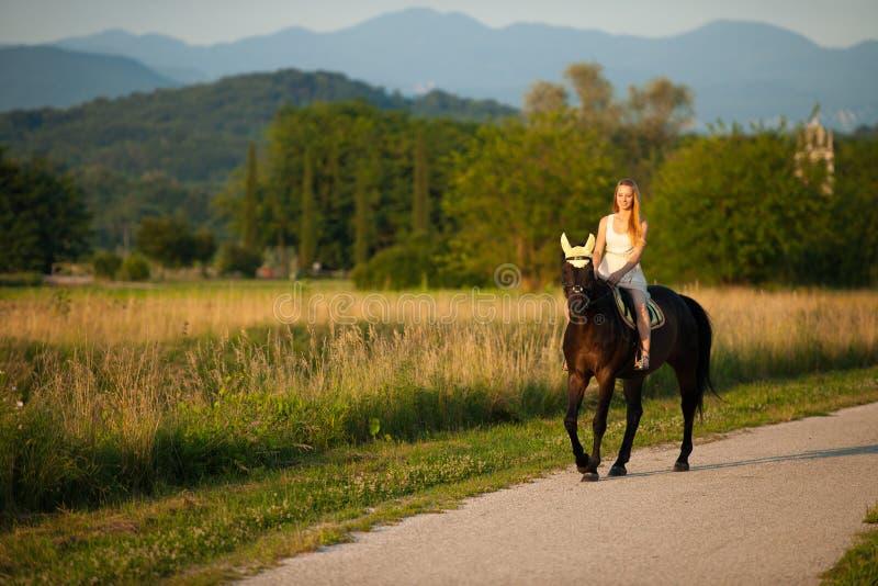 Giro attivo della giovane donna un cavallo in natura fotografie stock