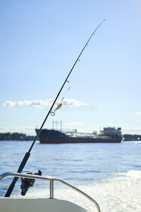 Giro con la pesca con cebo de cuchara con cebo de cuchara en el casco del ` s de la nave contra el fondo fotos de archivo libres de regalías