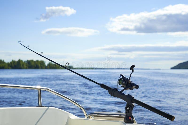 Giro con la pesca con cebo de cuchara con cebo de cuchara en el casco del ` s de la nave contra el fondo foto de archivo