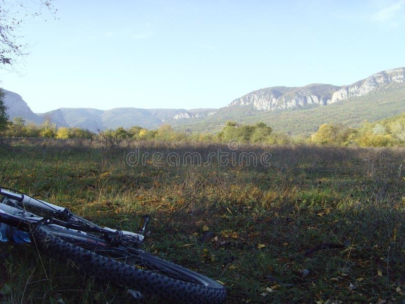 Giro della bici sul terreno della montagna La bici si trova sull'erba in un'area montagnosa immagine stock libera da diritti
