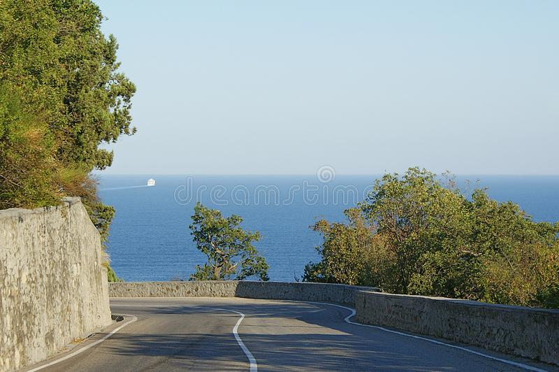 Giro della strada al mare ed al cielo blu del fondo immagini stock