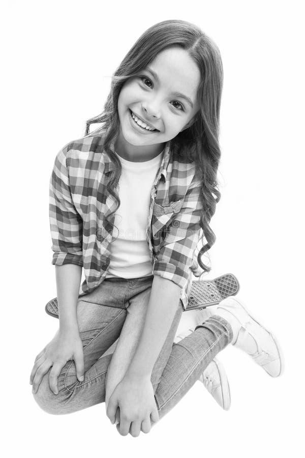 Giro felice La ragazza del bambino felice si siede il bordo del penny Originalmente progettato come le ragazze pattinano Hobby te immagine stock