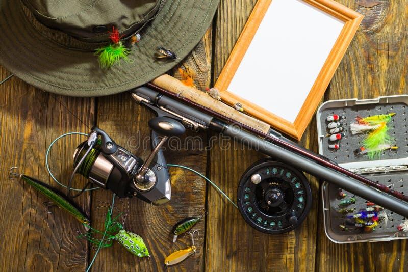 Giro, pesca com mosca, moscas, giradores, chapéu e quadro para sua etiqueta que encontra-se em uma tabela de madeira foto de stock