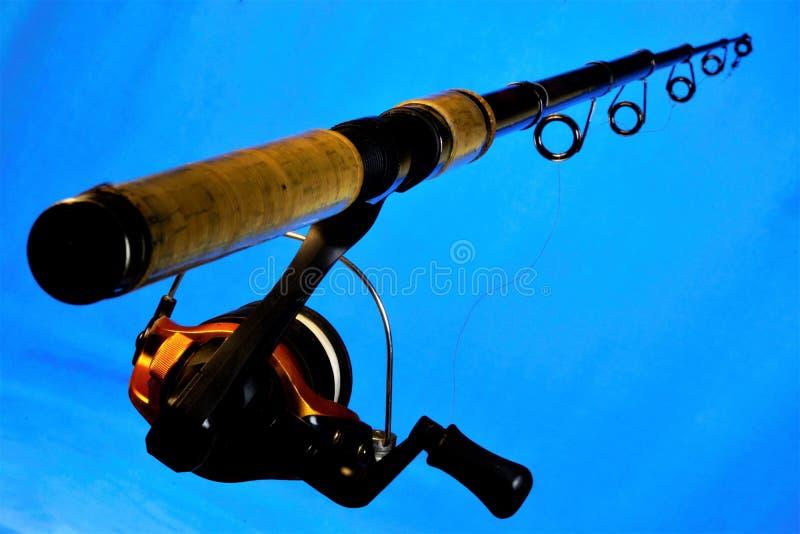 Giro - trastos de los deportes para pescar en cebo en un fondo azul Giro fácil en los cuerpos del agua para los señuelos de lan fotografía de archivo libre de regalías