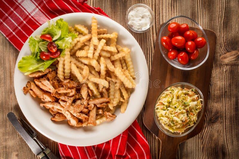 Girocompases griegos SID con las fritadas y la ensalada foto de archivo libre de regalías