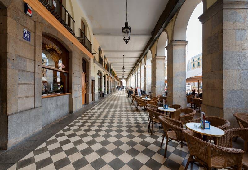 Girona, cuadrado de la independencia, arqueó el paso con los cafés fotografía de archivo