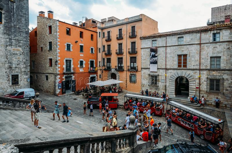 Red touristic train at the main square facing Cathedral of Saint Mary of Girona royalty free stock image