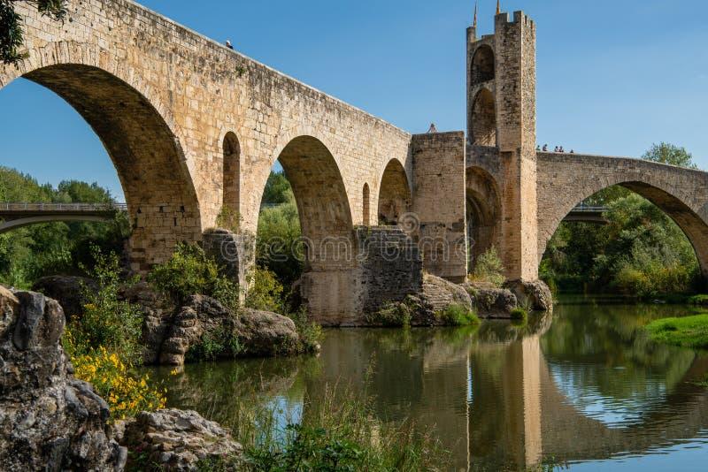 Girona Spanien - Sept 24 2018: Besk?da fr?n under romanesquebron ?ver den Fluvia floden med b?gar och f?rsvartorn i Besalu, arkivbilder