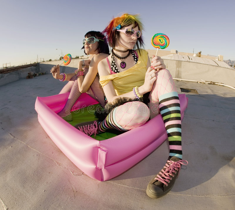 Girsl on a roof in a plastic pool. Fisheye shot of girls in brightly colored clothing in a plastic pool on a roof with sunglasses and lollipops stock image