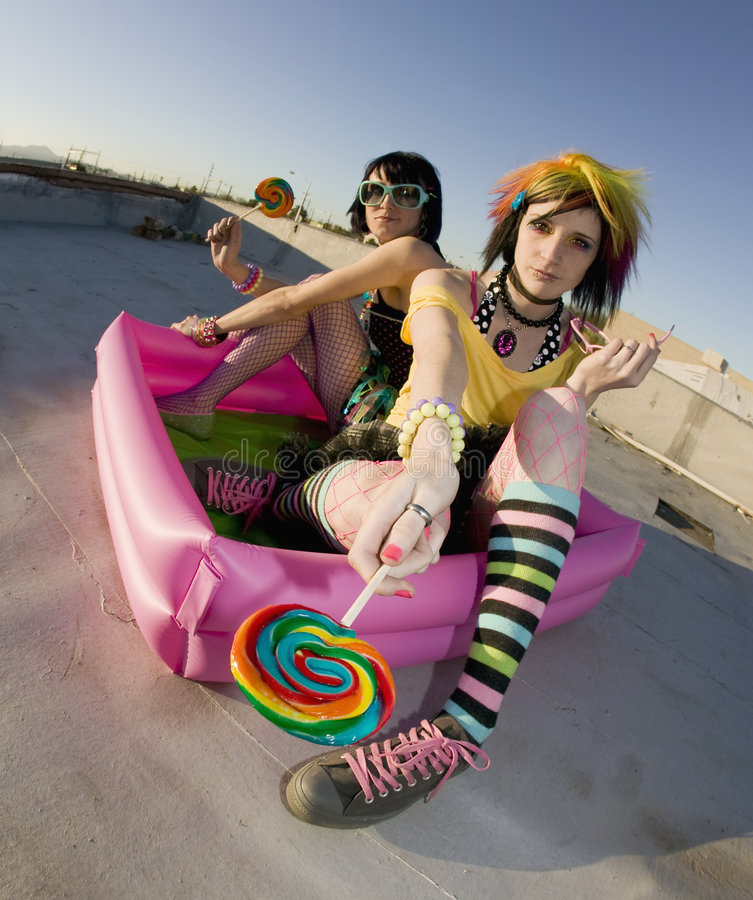 Girsl on a roof in a plastic pool. Fisheye shot of girls in brightly colored clothing in a plastic pool on a roof with lollipops stock images