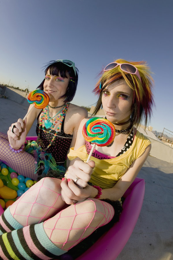 Girsl on a roof in a plastic pool. Fisheye shot of girls in brightly colored clothing in a plastic pool on a roof with sunglasses and lollipops royalty free stock photos