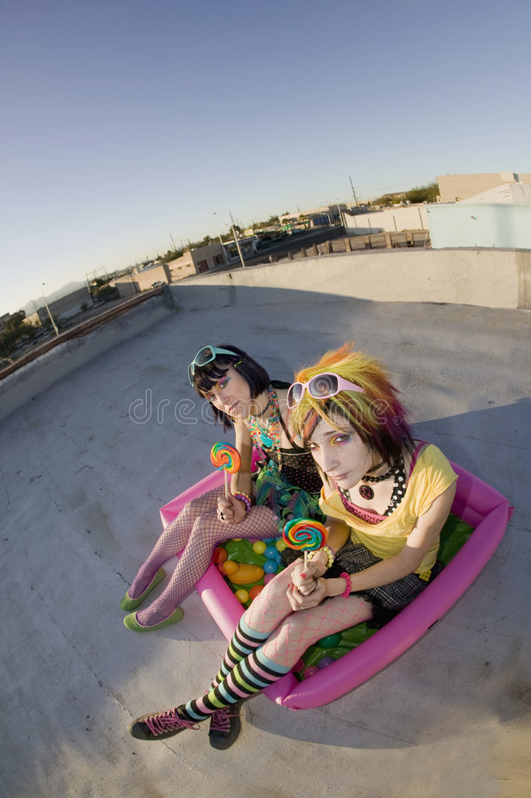 Girsl on a roof in a plastic pool. Fisheye shot of girls in brightly colored clothing in a plastic pool on a roof with sunglasses and lollipops stock photos