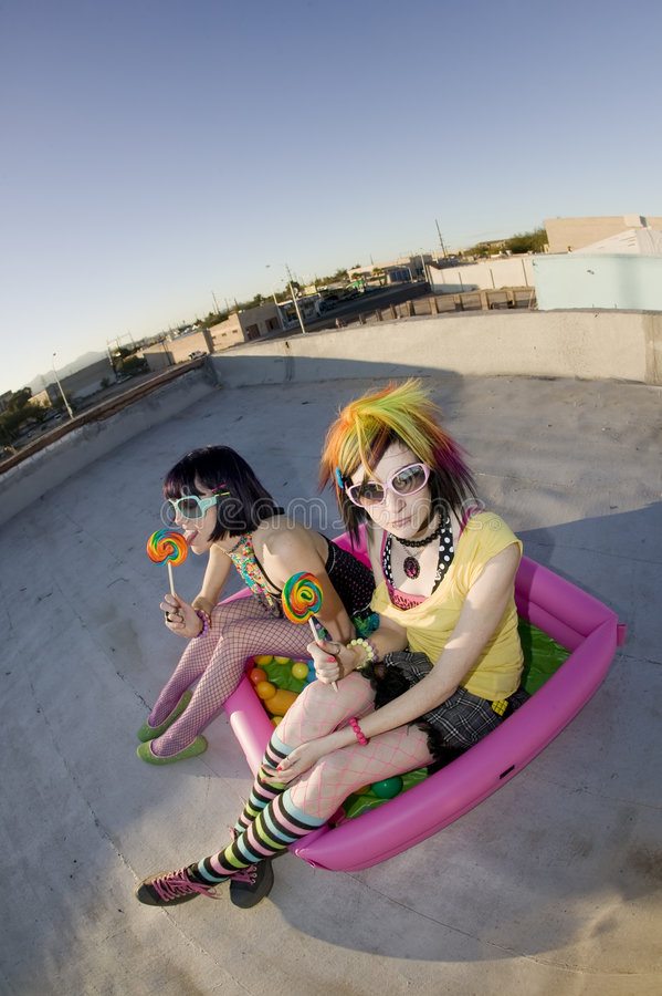 Girsl on a roof in a plastic pool. Fisheye shot of girls in brightly colored clothing in a plastic pool on a roof with sunglasses and lollipops stock photo