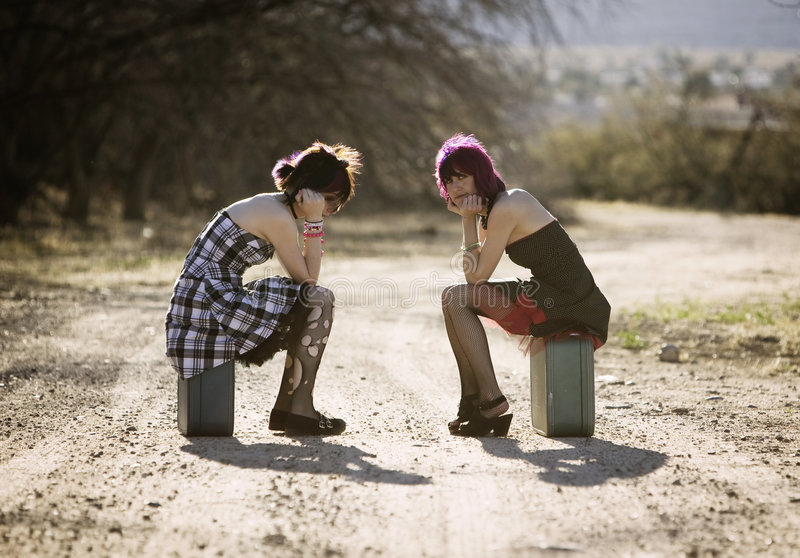 Girsl waiting on a rural road. Two punk women sitting on suitcases and waiting on a rural road stock photography