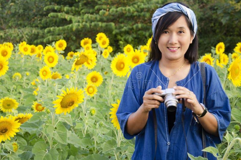 Gisement de fleur thaïlandais asiatique de tournesol de photo de tir d'appareil-photo d'utilisation de femme photo libre de droits