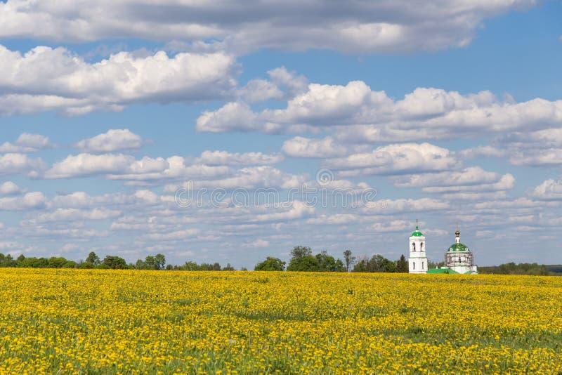 Gisement de ressort avec les fleurs jaunes et église, ciel bleu avec des nuages image libre de droits