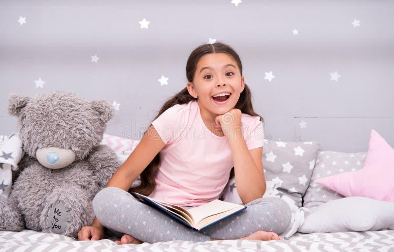 Gissa hennes favorit- saga Flickabarnet sitter säng med den lästa boken för nallebjörnen Ungen förbereder sig att gå att bädda ne arkivbilder