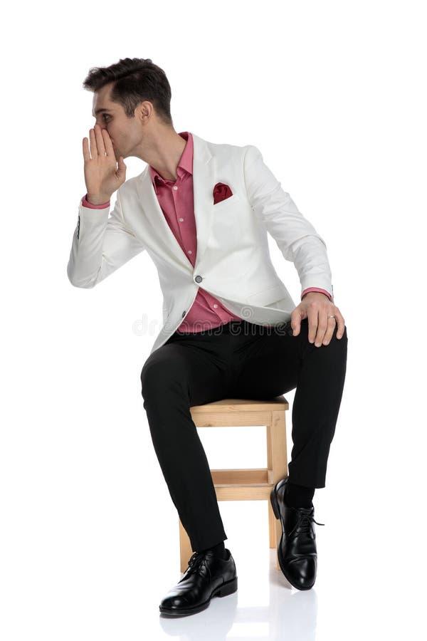 Gissip elegante joven de las charlas del hombre a su lado mientras que se sienta imagen de archivo libre de regalías