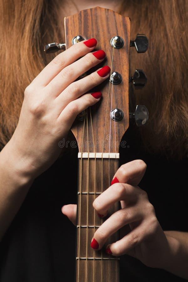 Gitaar in de handen van een vrouw die muzikaal instrument spelen royalty-vrije stock foto