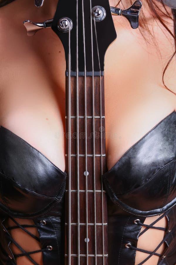 Gitaar fretboard tussen haar borsten wordt geklemd die stock afbeeldingen