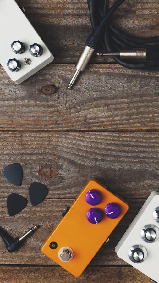 Gitaarpedalen en toebehoren op houten vloer stock foto's