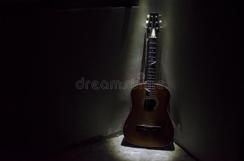 Gitara akustyczna opiera na ośniedziałej ścianie w ciemnym pokoju z światłami Surrealistyczny widok pokój z gitary Długie ujawnie fotografia stock