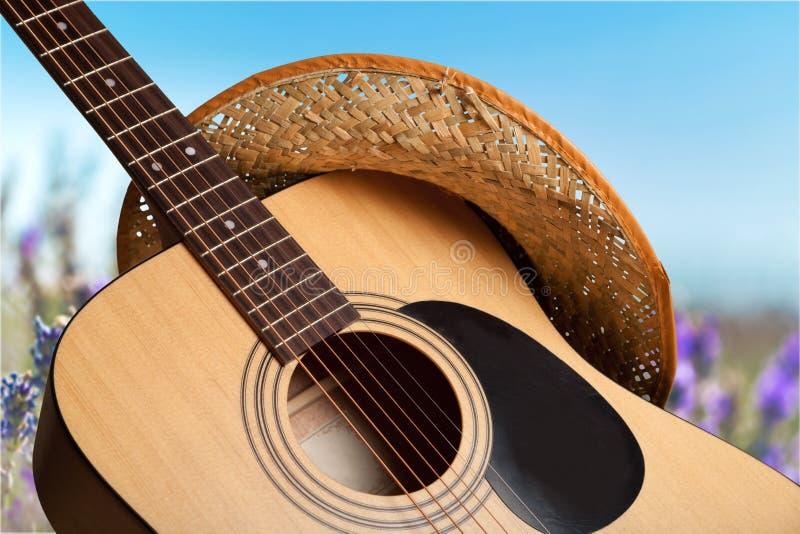 Gitara akustyczna z kapeluszem na lekkim tle zdjęcie royalty free