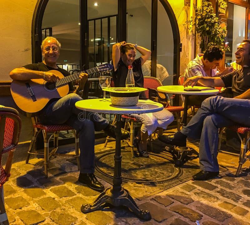 Gitara gracz ono uśmiecha się przy kamerą podczas gdy para cieszy się moment przy plenerową kawiarnią w Paryż zdjęcia stock