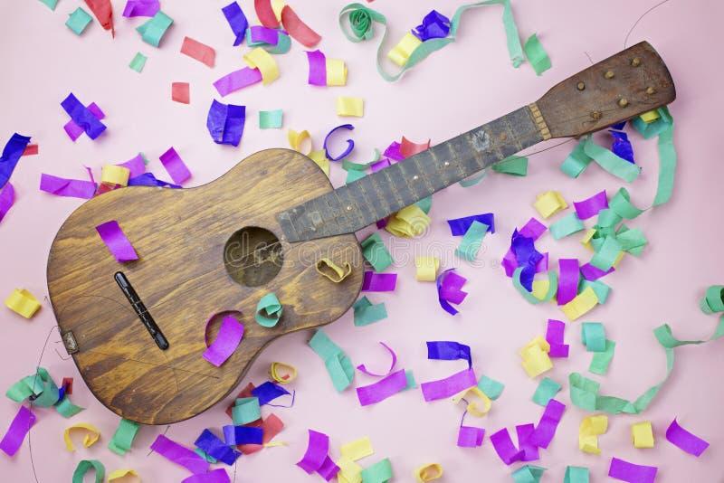 Gitara kłama w barwiącym świecidełku na różowym tle obraz royalty free
