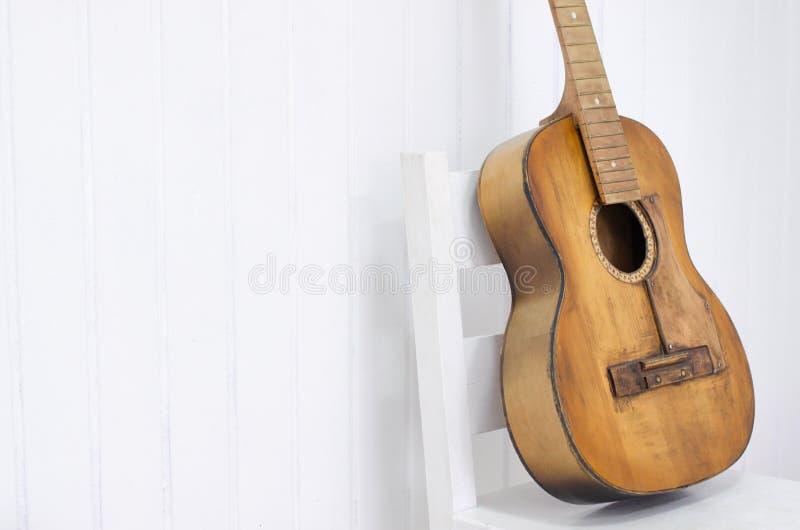 Gitara na białym krześle białym tle i zdjęcie stock