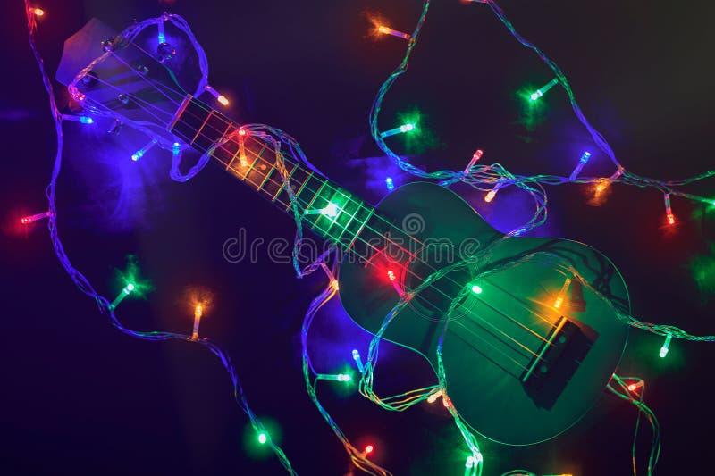 Gitara na tle barwioni światła Rozblaskowi światła girlanda i ukulele zdjęcie stock