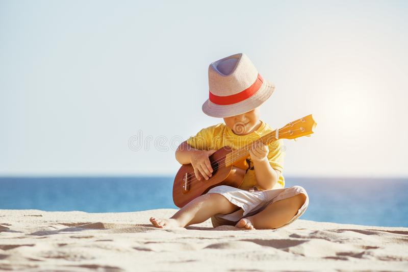 Gitara ukulele pojęcie z chłopiec przy plażą obraz stock