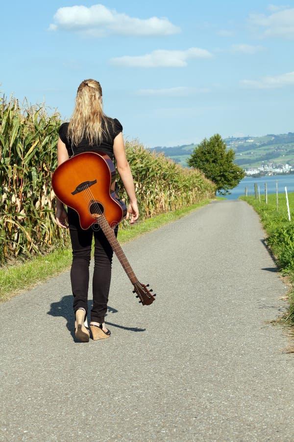 Gitarist die onderaan landweg loopt royalty-vrije stock afbeelding