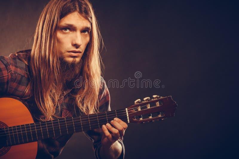 Gitarist die snaren uitproberen stock foto