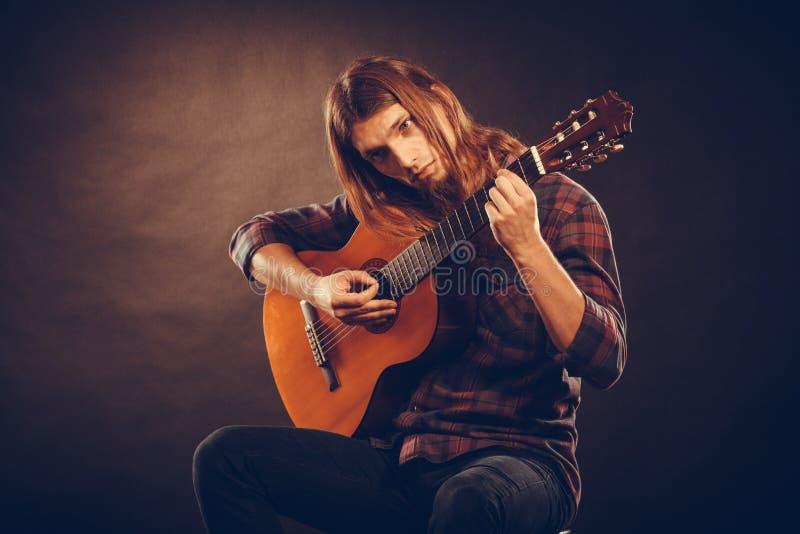 Gitarist die snaren uitproberen stock fotografie