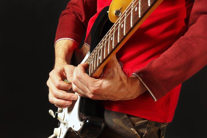 Gitarist gezette vingers voor snaren op elektrische gitaar op zwarte achtergrond stock foto