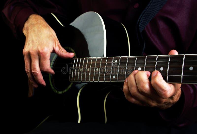 Gitaristhanden en gitaar royalty-vrije stock afbeeldingen