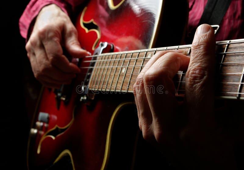 Gitaristhanden en gitaar royalty-vrije stock afbeelding
