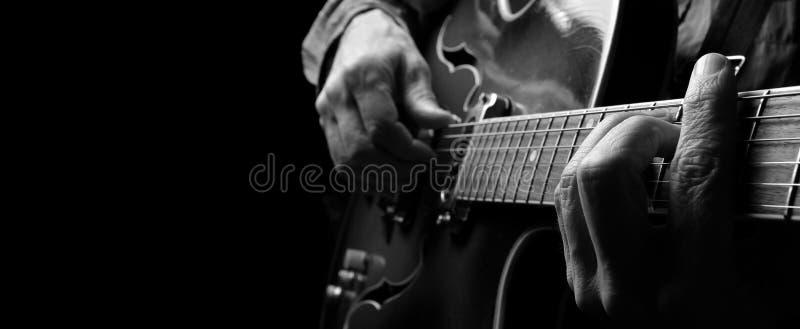 Gitaristhanden en gitaar stock afbeelding