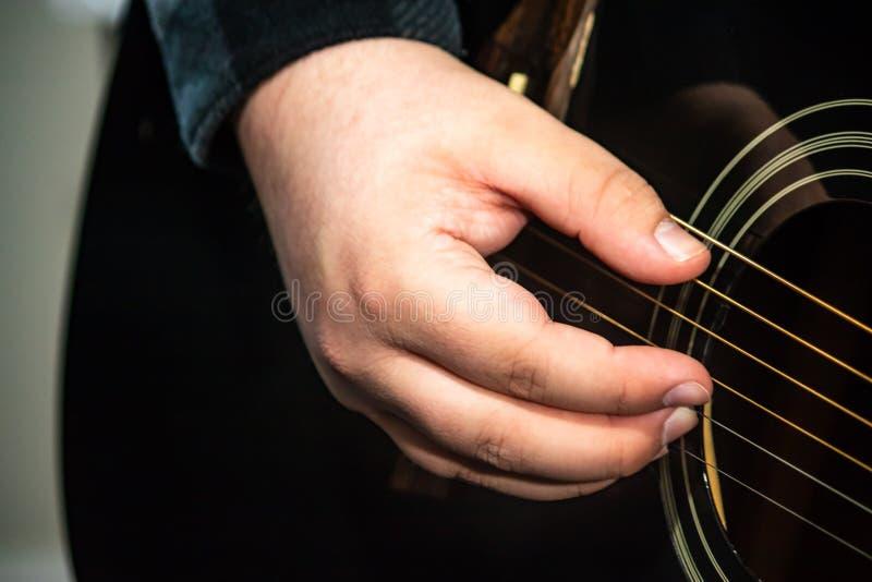 Gitaristvinger die een gitaar plukken stock afbeelding