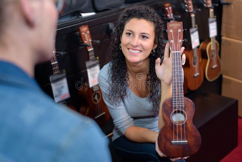 Gitarr för kvinnavisningminiatyr fotografering för bildbyråer