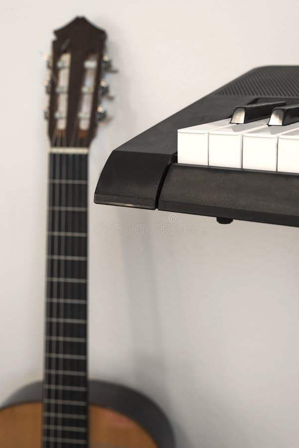 Gitarr och del av pianotangentbordet som isoleras på vit arkivbild