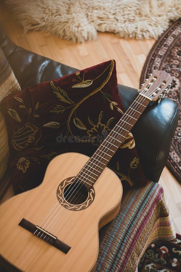 Gitarr och kudde som f?rl?ggas p? soffan p? vardagsrum arkivfoto