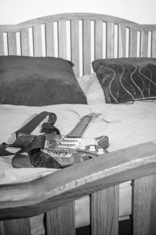 Gitarre auf Bett lizenzfreies stockfoto
