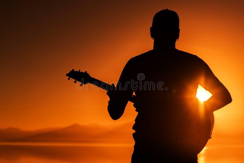 Gitarre, die bei Sonnenuntergang spielt lizenzfreies stockfoto