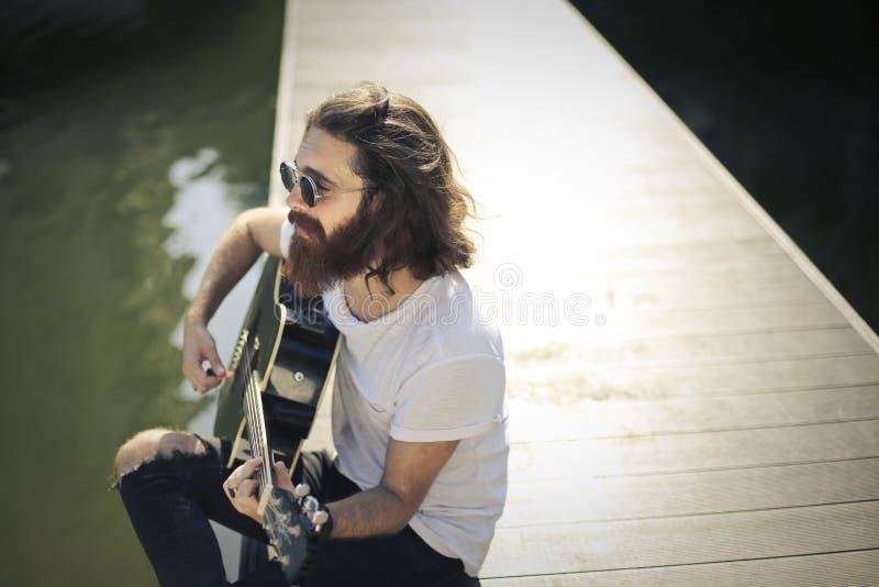Gitarre, die in einem Park spielt lizenzfreie stockbilder