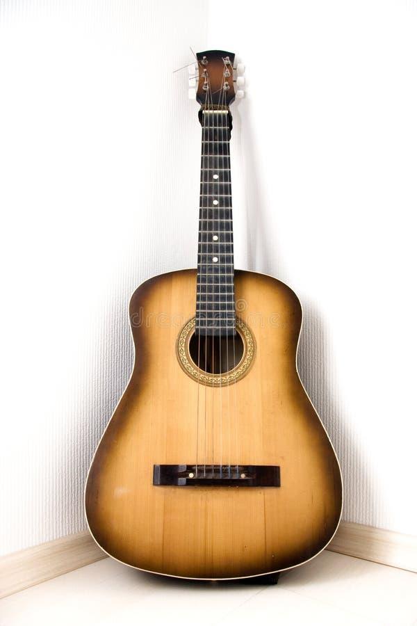Gitarre in einer Ecke des Raumes lizenzfreie stockbilder